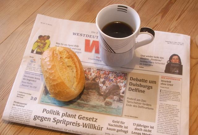 Tageszeitung mit Kaffee und Brötchen